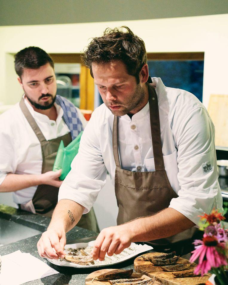 De chef en zijn medewerker aan het werk in de keuken van de gastvrouw. Beeld Joris Casaer