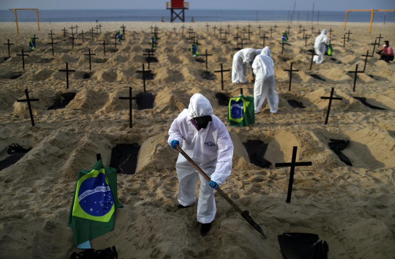 Activisten graven een kerkhof op het strand van Copacabana in Rio de Janeiro om de doden te symboliseren die door het beleid van president Bolsonaro vallen. Beeld Reuters