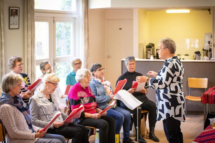 Gertie Savelkoul dirigeert de zangers.