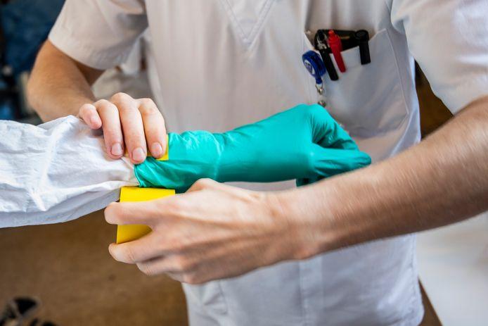 Beeld corona-afdeling OLV: verplegend personeel maakt zich klaar om de afdeling binnen te gaan.