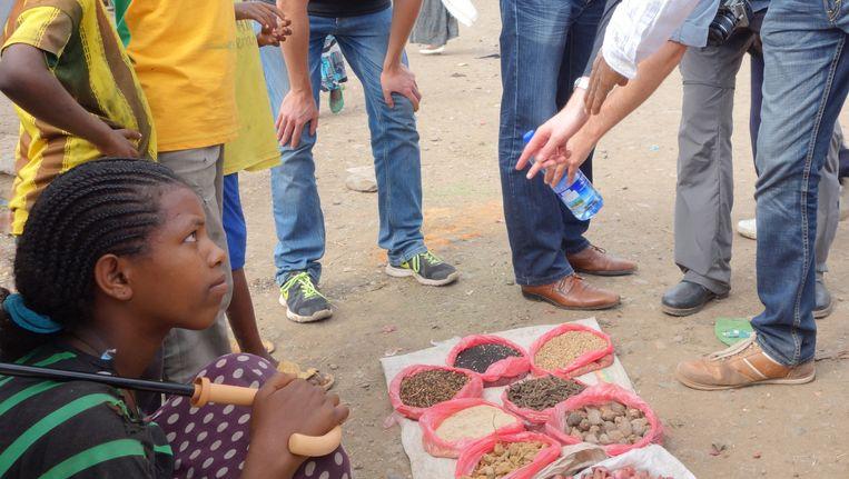 Een straatverkoopster van sesam en andere zaden en kruiden trekt de aandacht van de Nederlandse handelsmissie in het dorp Sanja. Beeld Wim Bossema