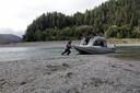 Een visser van de Yurok duwt zijn boot het water van de Klamath in.