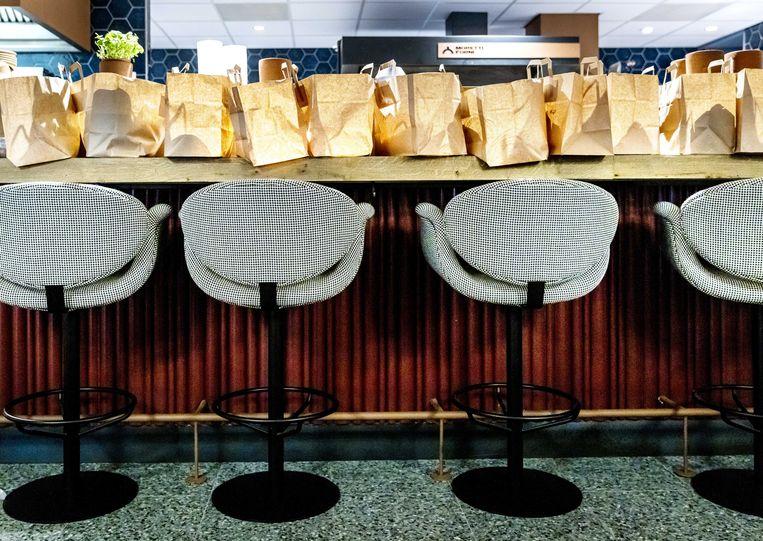 Tassen met afhaal- en bezorgmaaltijden op de bar in restaurant No Rules in Amsterdam. Door de coronamaatregelen mag er niet in het restaurant worden gegeten. Beeld ANP, Remko de Waal