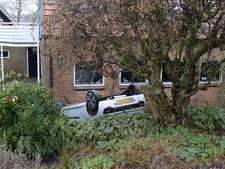 Auto rijdt van dijk en belandt op de kop in een tuin