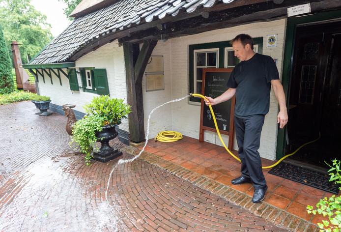 Eigenaar André Licht rest niets anders dan de vele liters regenwater uit zijn restaurant te pompen.