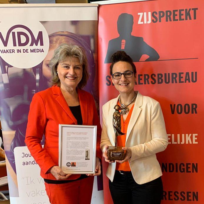 Sandra de Blaeij (rechts) ontvangt de trofee en de oorkonde die horen bij de Vrouw in de Media Award. Links: Marga Miltenburg van ZijSpreekt.