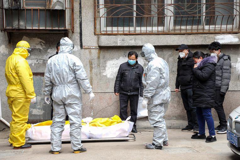 Een coronaslachtoffer wordt uit zijn huis in Wuhan gedragen. Beeld EPA