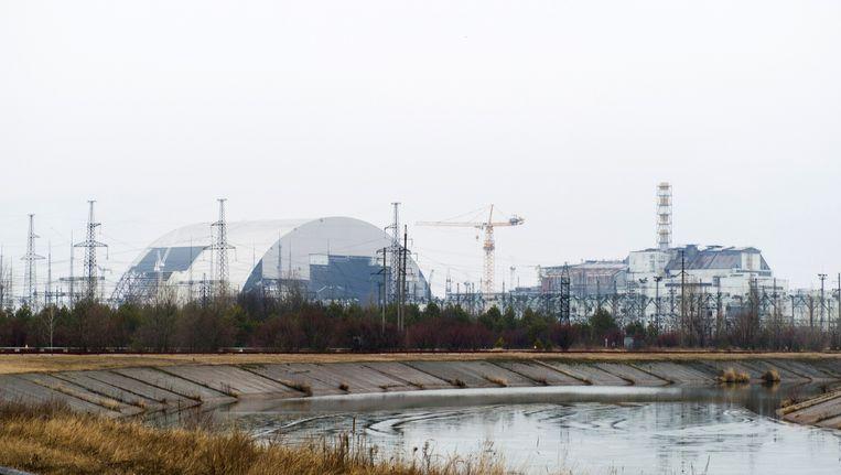 Over het reactorgebouw in Tsjernobyl wordt een koepel gebouwd die moet vermijden dat er nog meer radioactief materiaal kan lekken. Beeld AFP