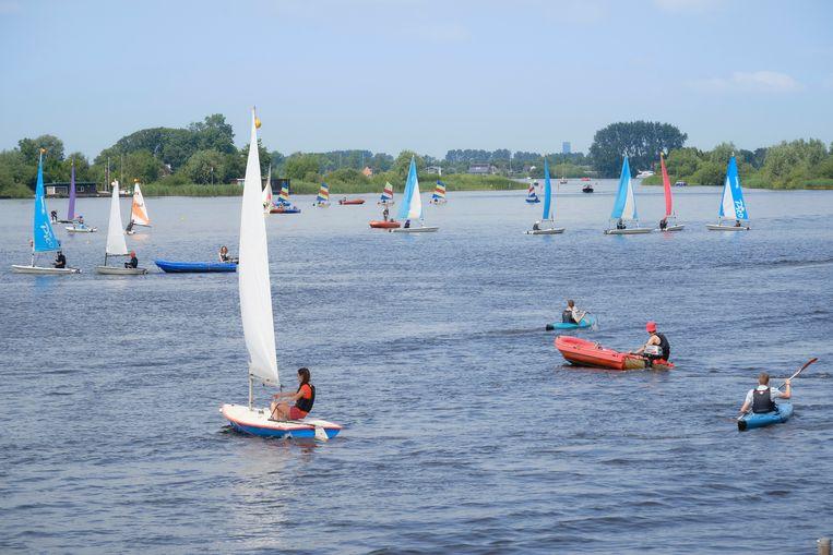 De cursisten van het zeilkamp in het Friese Akkrum-Nes varen rond in kleine groepjes, terwijl instructeurs en de leiding in oranje motorbootjes en kano's tussen ze door varen. Beeld Sjaak Verboom