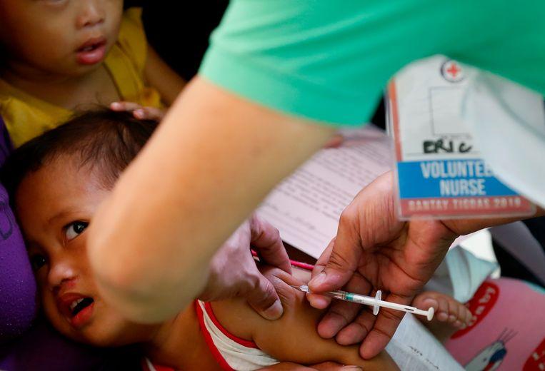 Vrijwilligers van het Filipijnse Rode Kruis gaan van huis tot huis om kinderen te vaccineren  Beeld AP