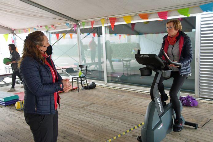 Eigenaresse Sandra Hanel (mondkapje) van sportcentrum Delta en Jolanda Rottier-van de Brande genieten van het persoonlijk contact na maanden zoomles.