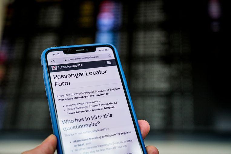 Het Passenger Locator Form in het Engels te zien op een smartphone op Brussels Airport. Archiefbeeld ter illustratie. Beeld BELGA