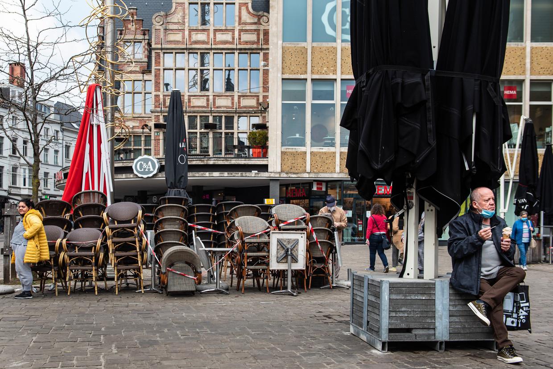 Tafeltjes, stoelen en passanten in Gent wachten in spanning op de heropening van de caféterrassen. Beeld Wouter Maeckelberghe