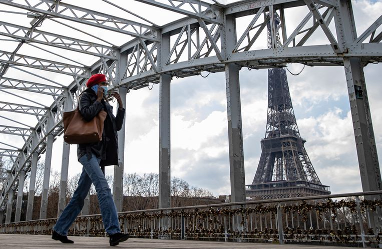 Een voetganger draagt een mondkapje vlak bij de Eiffeltoren in Parijs. De Franse premier Castex heeft extra maatregelen afgekondigd, omdat het land kampt met een derde golf van de pandemie.  Beeld EPA