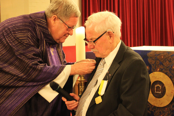 Pastor Rekveld speldt Jan Hesselink de pauselijke onderscheiding op.