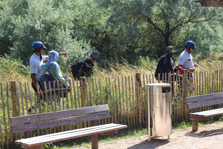 Enkele transmigranten worden weggeleid door de politie.