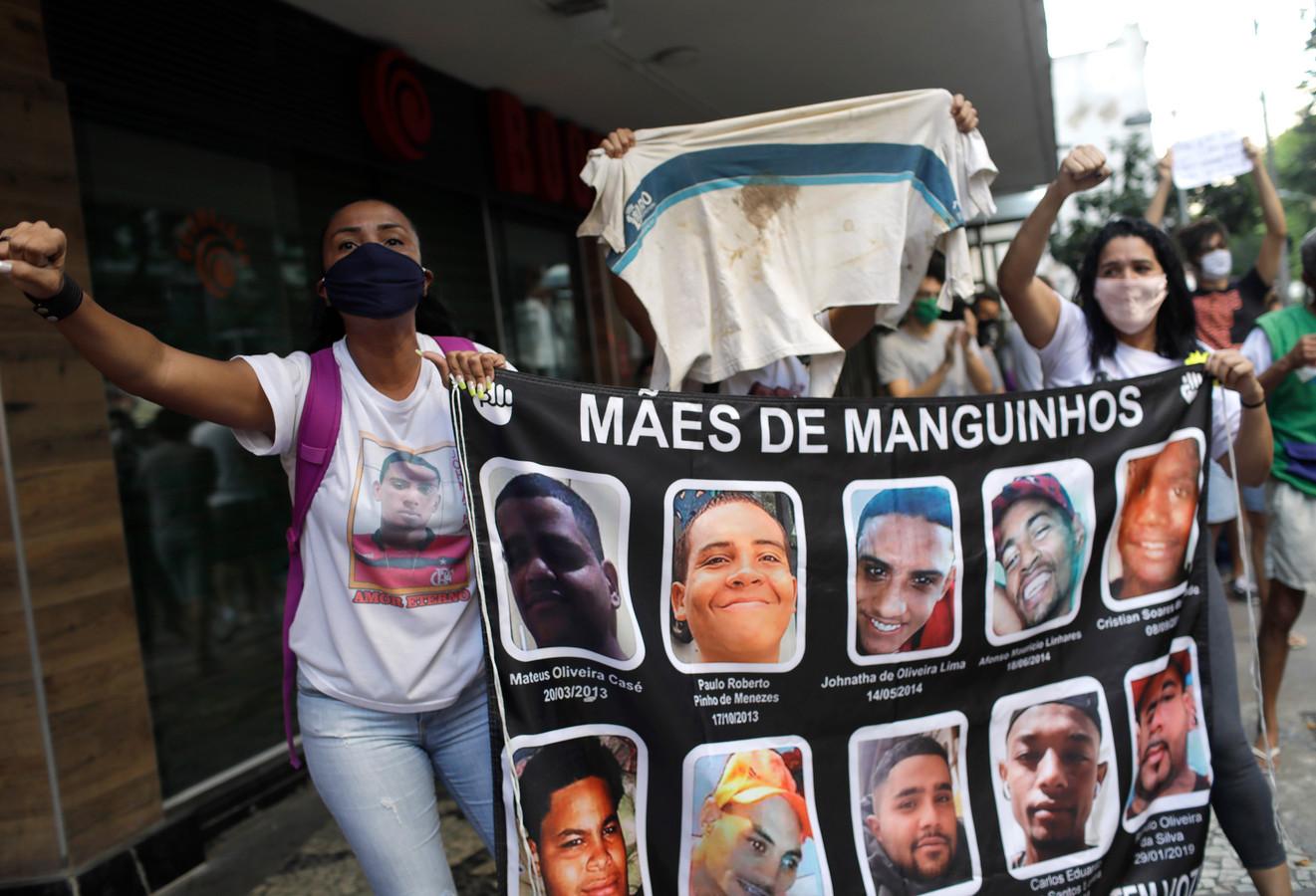 Moeders wier zonen werden gedood tijdens politie-acties in de sloppenwijken, tonen op een spandoek de foto's en namen van de jongens tijdens de betoging in Rio de Janeiro.
