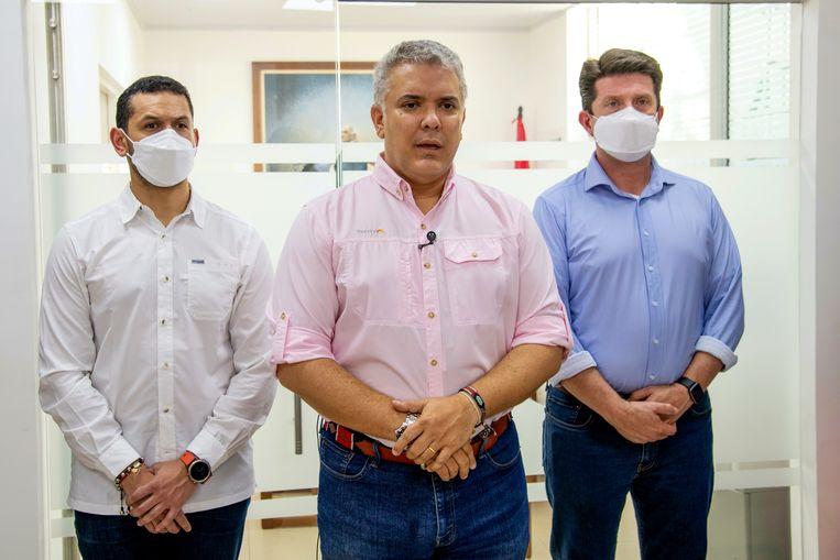 De Colombiaanse president Ivan Duque staat na de aanslag op zijn helikopter de pers te woord, geflankeerd door minister Palacios van Binnenlandse Zaken (links) en minister van Defensie Molano. Beeld AP