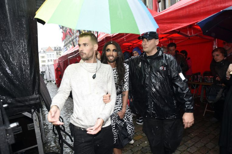 Eurosongwinnaar Conchita Wurst stapt in de gietende regen onder begeleiding naar het podium.