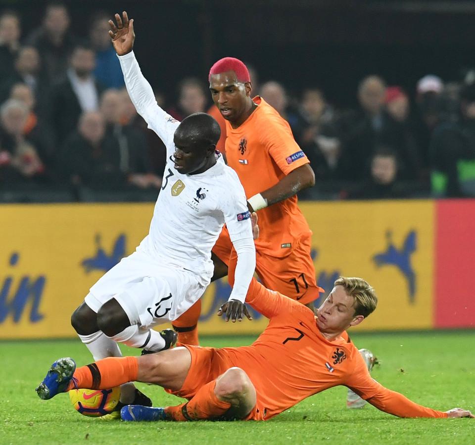 Ryan Babel kijkt toe hoe Frenkie de Jong in de Kuip de Fransman N'golo Kanté van de bal probeert te zetten.