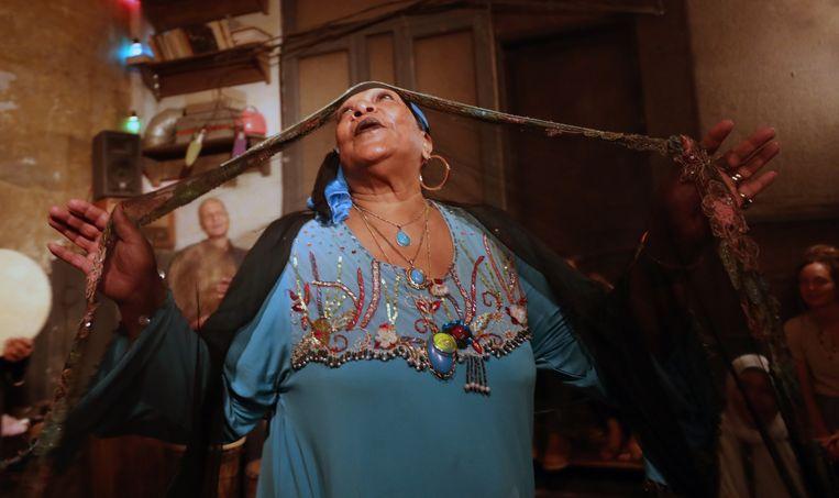 De Egyptische Umm Sameh is een van de laatste beoefenaars van Zar, een muzikaal genezingsritueel waarbij gedrumd en gedanst wordt. Met haar ensemble Mazaher, dat grotendeels bestaat uit vrouwen, treedt ze hier op in Cairo. Beeld EPA