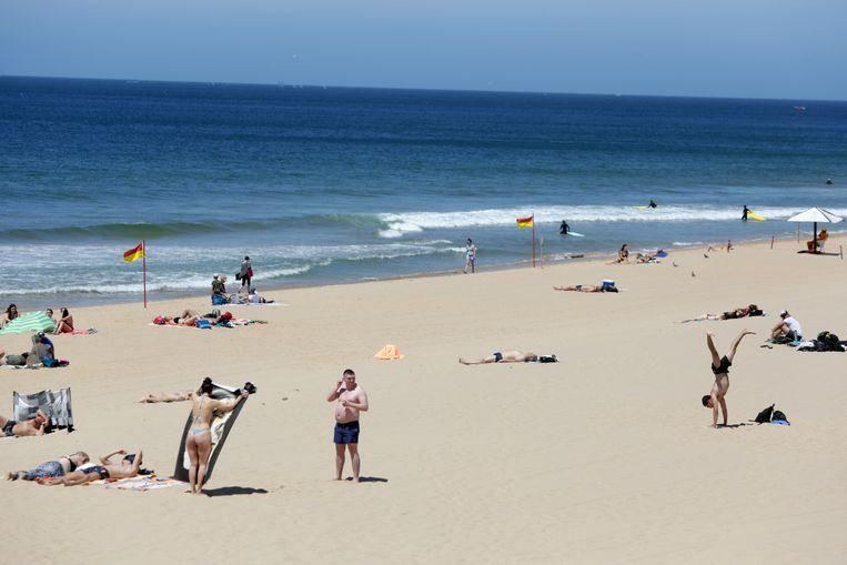 Vakantiegangers op een strand bij Cascais, bij Lissabon.  Beeld AP