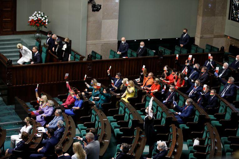 Bij de beëdiging Andrzej Duda voor een tweede termijn als president van Polen, afgelopen augustus, dragen parlementariërs regenboog-mondkapjes uit protest tegen zijn intolerante standpunten over homoseksualiteit.  Beeld Reuters