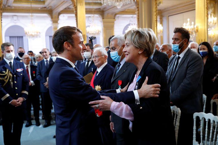 Emmanuel Macron met Borinia Tarall, voorzitter van een vrouwenorganisatie, tijdens de herdenkingsbijeenkomst ter nagedachtenis aan de harki's in Parijs. Beeld EPA