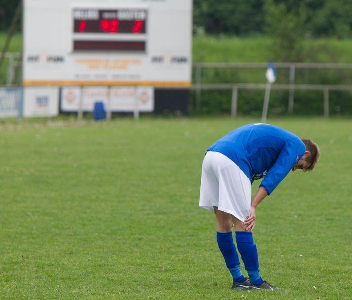 Een voetballer van Helios uit Deventer baalt na een verloren wedstrijd.