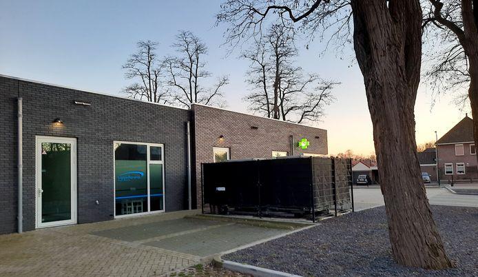 Zijgevel van Gezondheidscentrum Heesch met daarnaast, met een doek er omheen, de vier warmtepompen.