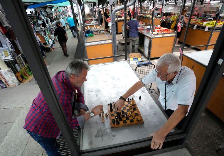 Twee mannen schaken op de groene markt van Belgrado (Servië). Beeld AP