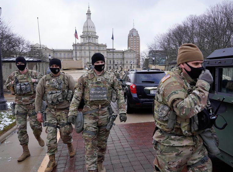Leden van de Nationale Garde maken zich gereed voor de komst van (gewapende) demonstranten bij het regeringscentrum in de hoofdstad van de staat Michigan.  Beeld AP