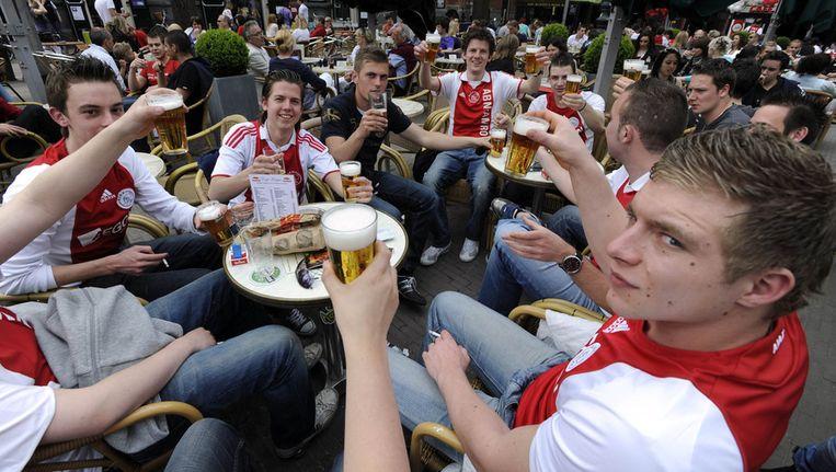 Fans van Ajax zitten op het Leidseplein een biertje te drinken. Vanaf nu mogen ze dat ook weer staand doen. Beeld ANP
