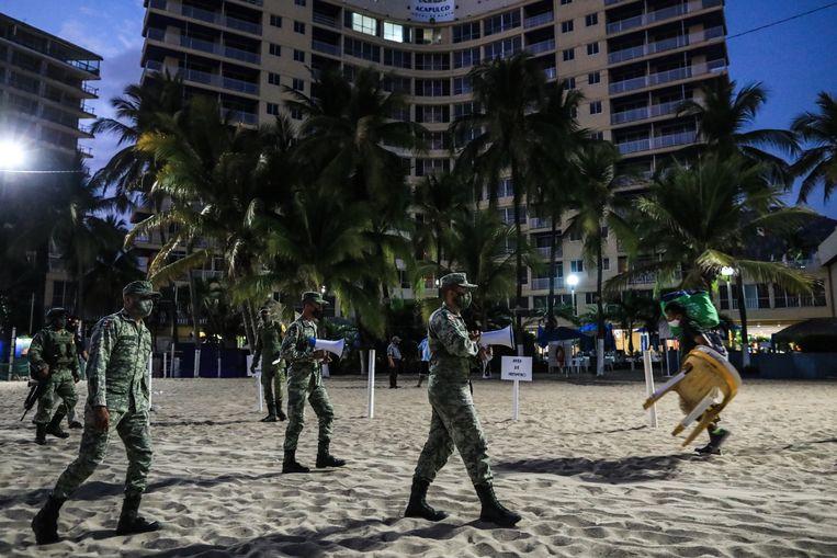 Militairen helpen bij het schoonvegen van het strand in Acapulco, Mexico. Beeld EPA