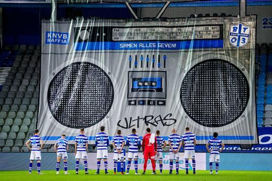 De spelers van De Graafschap luisteren, staand voor het spandoek, naar de 'radioboodschap' van Brigata Tifosi.