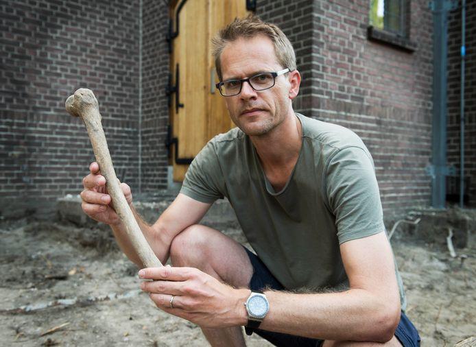 Jaap Breugem met een menselijk bot dat hij vond bij de Marekerk in De Meern.