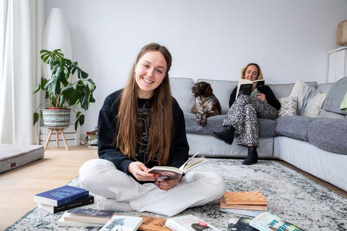 """Rubriek: """"Ik zeg je"""" over 17 jarigen. Op de foto: Vienne Haagoort in haar woonkamer met haar favoriete boek. Op de achtergrond haar moeder Danielle (zonder puntjes op de e) en haar hond Mila."""