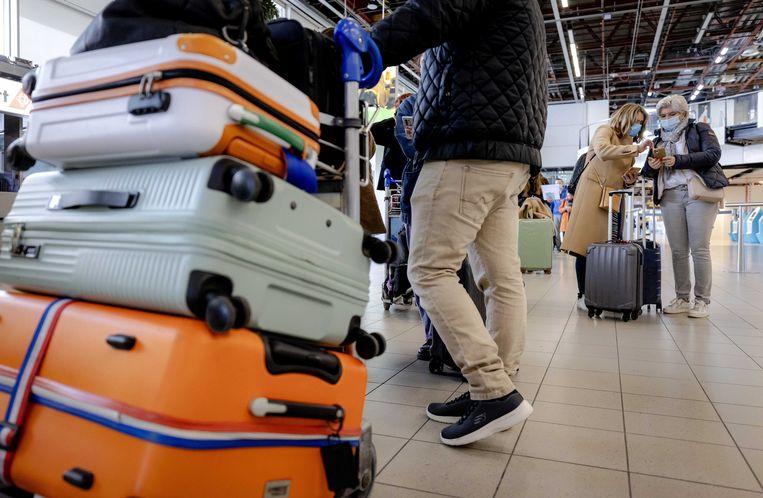 Reizigers bij de incheck-balie op luchthaven Schiphol. Beeld EPA, Robin van Lonkhuijsen