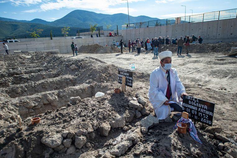 Een imam woont de begrafenis bij van Bayram en Hatice Dogruya, twee slachtoffers van de aardbeving in Izmir. Beeld AFP