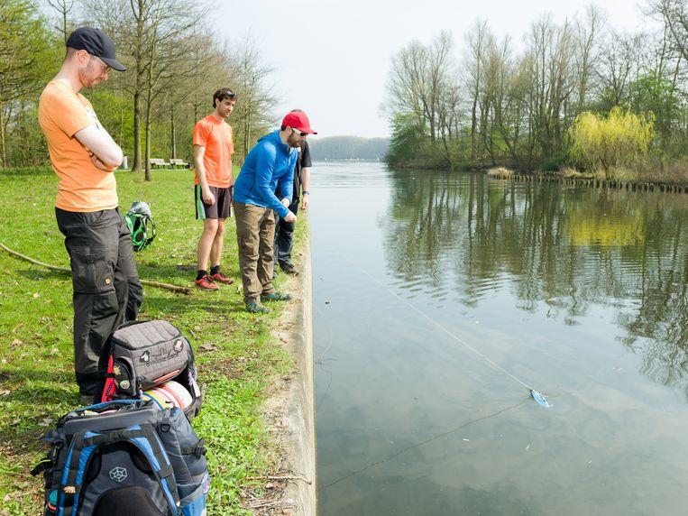 Dean Schaub (met blauwe trui) vist een frisbee uit het water. Links vooraan Paul Sterk. Beeld Ivo van der Bent