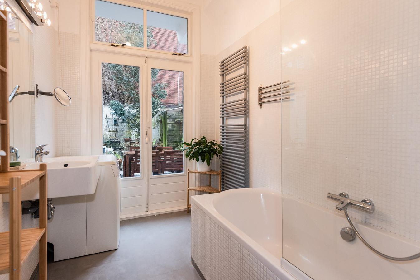De badkamer met openslaande deuren naar de tuin.