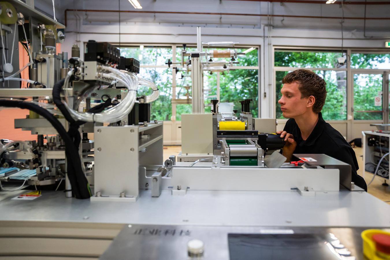 Enrico van de Vliert van het Arnhemse ingenieursbedrijf QING installeert een van de machines voor de Mondmaskerfabriek.