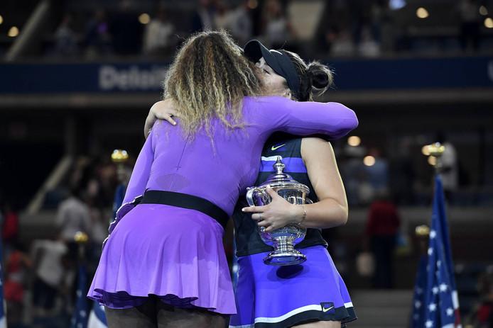 Bianca Andreescu (met beker) en Serena Williams na de finale van de US Open.