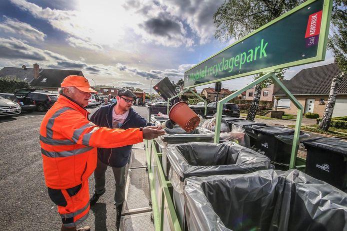 Mensen komen iets deponeren in een mobiel recyclagepark.
