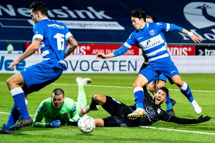 Een ouderwetse scrimmage voor het doel van PEC Zwolle. Terwijl doelman Michael Zetterer languit gaat en Sam Kersten (links) en Sai van Wermeskerken (rechts) tot het uiterste gaan, schreeuwt Heracles-speler Ismail Azzaoui - tevergeefs - om een penalty.