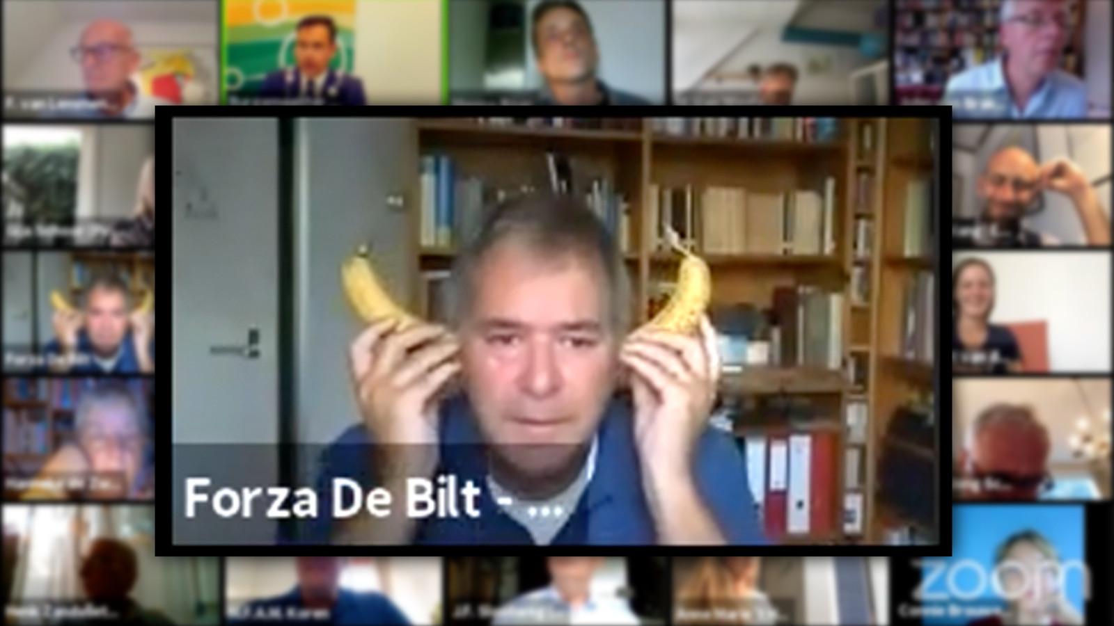 Peter Schlamilch van Forza De Bilt steekt bananen in zijn oren tijdens een digitale raadsvergadering.