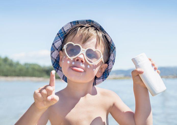 Een kind houdt een fles zonnecrème vast.
