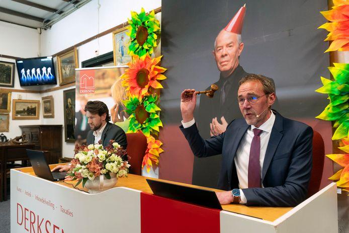 Albert Keddeman van Veilinghuis Derksen veilt spullen van Introdans. Op de achtergrond een foto van Hans van Manen, gemaakt door Erwin Olaf, die voor 440 euro van de hand ging.
