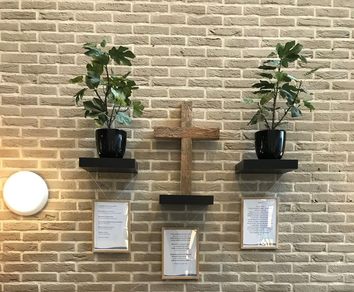 Een wand van de herdenkingsplek in De Haven is uitgerust met een kruis en enkele troostrijke gedichten.