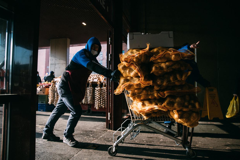 Een man brengt aardappels naar het gesloten gedeelte van de Odor markt in Boekarest waar de ramen aan de zijkant van het gebouw vanwege covid open blijven. Beeld Marlena Waldthausen